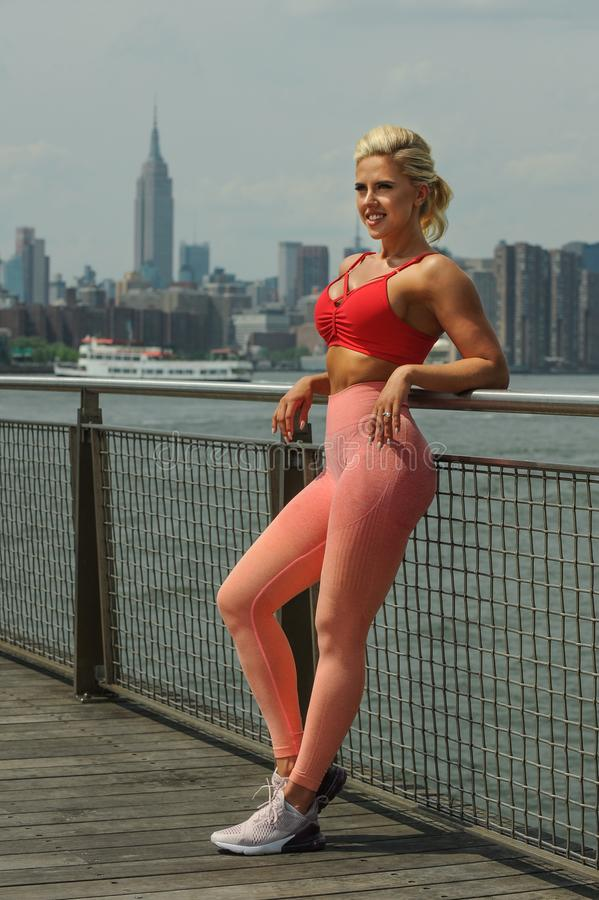 Attractive fit young woman dressed in bright sportswear posing outdoors. royalty free stock image