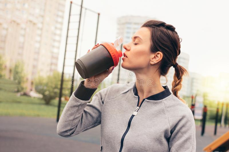 Attractive fit young woman in sport wear drink water and rest on street workout area. The healthy lifestyle in city. Attractive fit young woman in sport wear stock photography