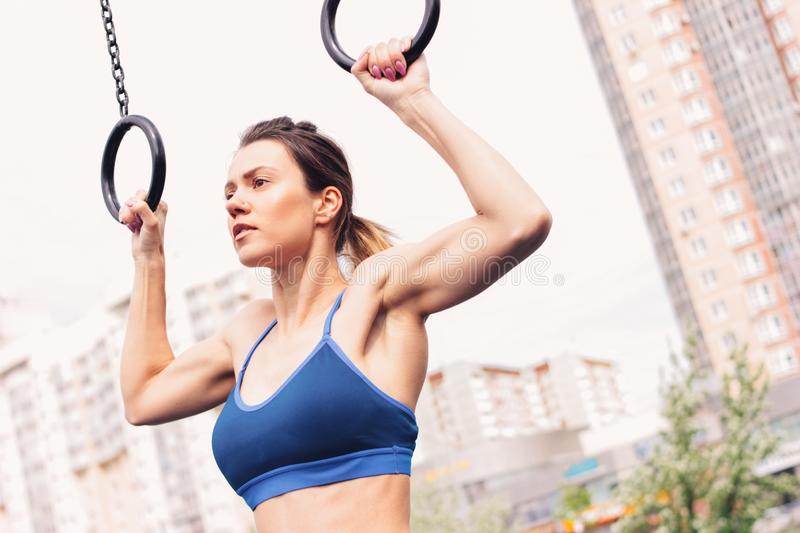 Attractive fit young woman in sport wear girl pulls up on the rings at street workout area. The healthy lifestyle in stock images
