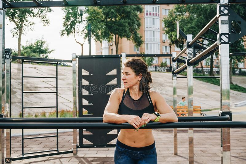 Attractive fit young woman in sport wear rest on the street workout area. The healthy lifestyle in the city. Street portrait royalty free stock image