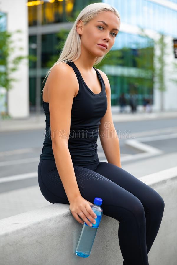 Attractive fit young woman dressed in black sportswear sitting outdoors royalty free stock images