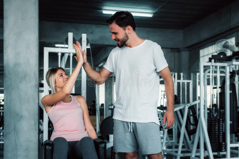 Attractive fitness couple love giving high five together after workout in fitness gym., Portrait of man and woman sporty are royalty free stock photos