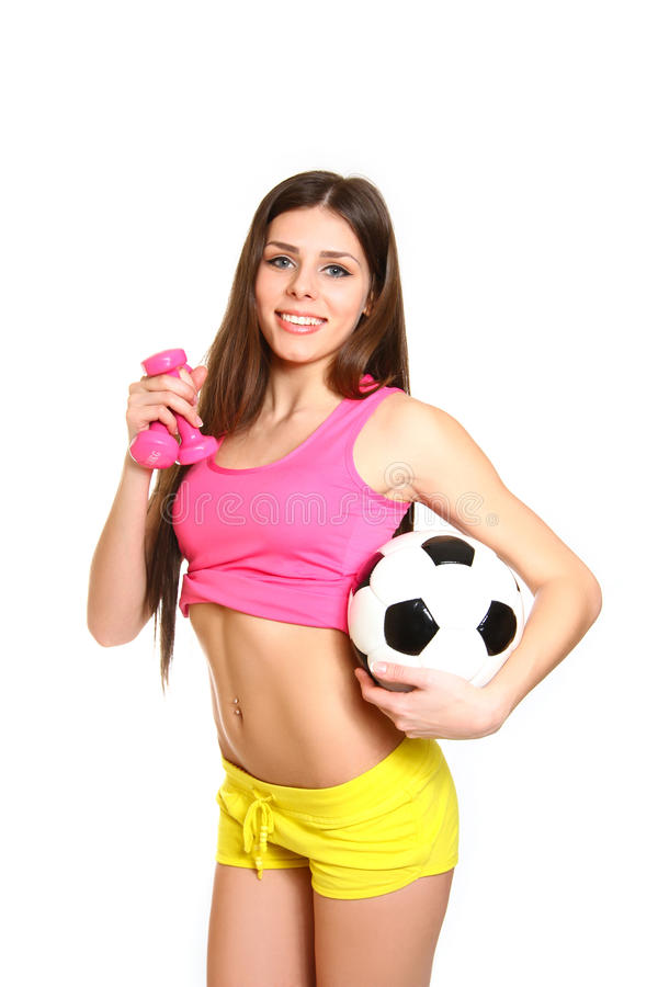 Attractive fitness girl with dumbbells and a soccer ball on a white background royalty free stock photos
