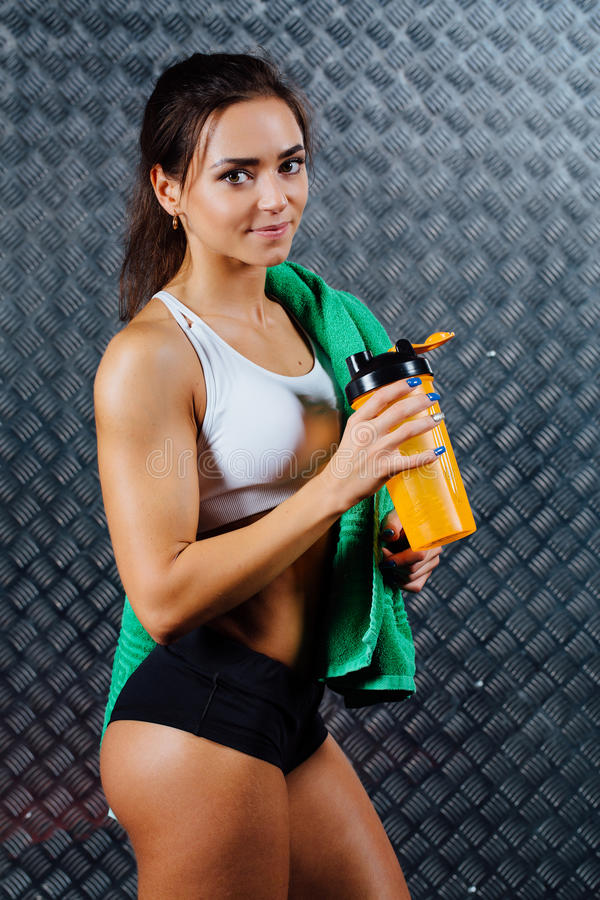 Attractive fitness woman with bottle and towel indoor portrait. royalty free stock images