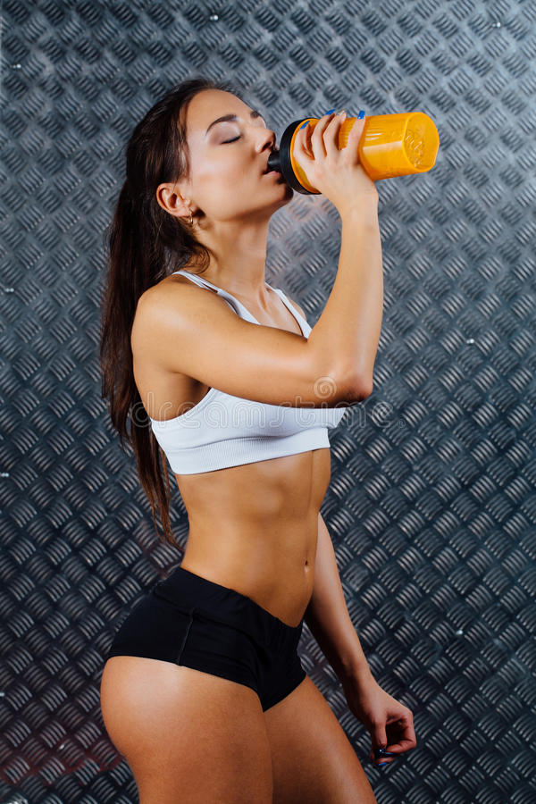 Attractive fitness woman indoor portrait with bottle. royalty free stock images