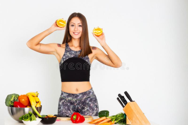 Attractive fitness woman, trained female Fit power athletic confident young woman bodybuilder cuting orange, Organic Food. royalty free stock photography