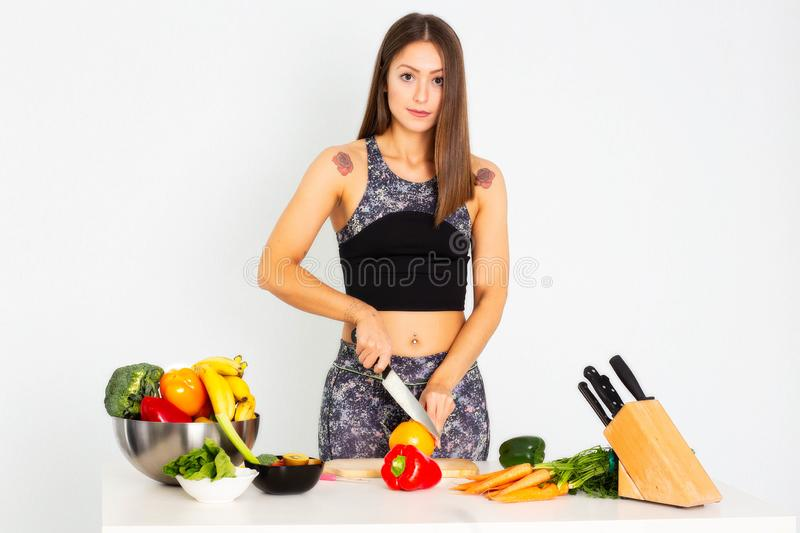 Attractive fitness woman, trained female Fit power athletic confident young woman bodybuilder cuting orange, Organic Food. Attractive fitness woman with a knife royalty free stock photos