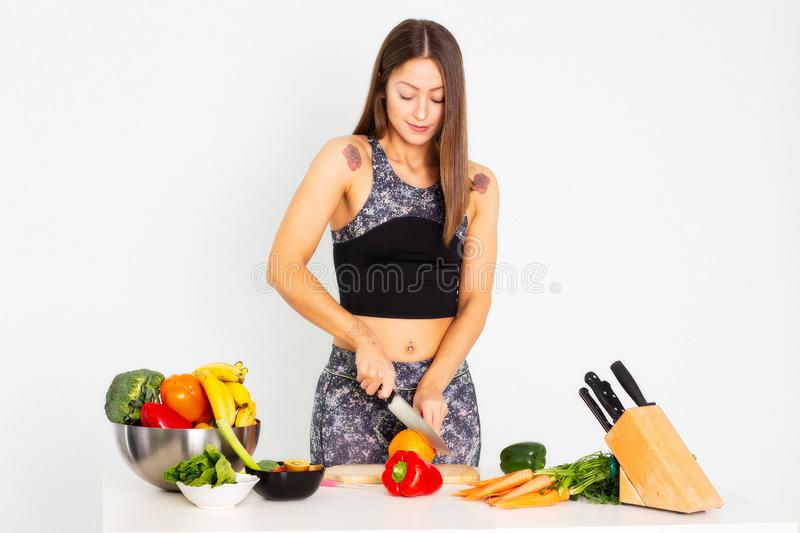 Attractive fitness woman, trained female Fit power athletic confident young woman bodybuilder cuting orange, Organic Food. Attractive fitness woman with a knife stock photo