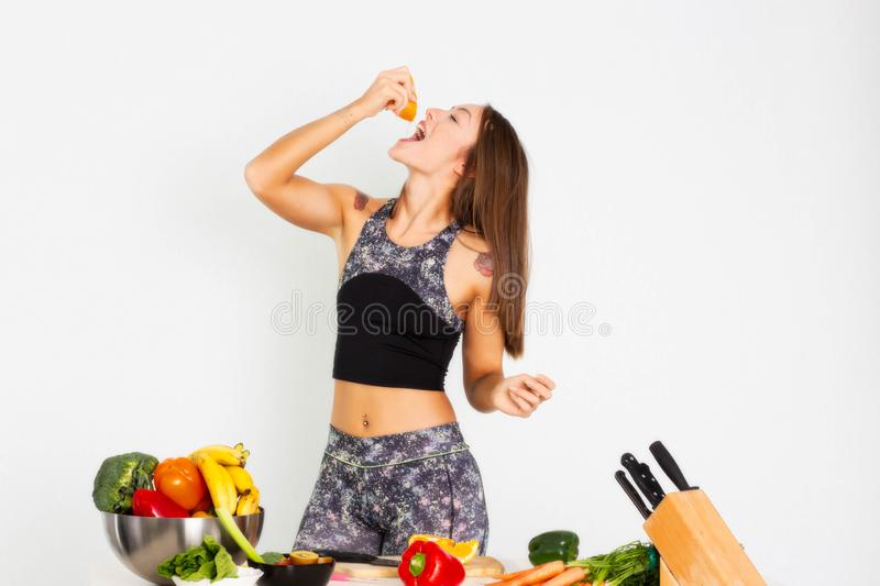 Attractive fitness woman, trained female Fit power athletic confident young woman bodybuilder eating orange, Organic Food. Attractive fitness woman with a knife stock photo