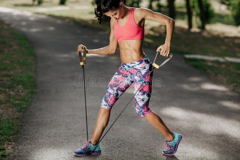 Attractive fitness young woman exercising with resistance band oudoor. Attractive fitness young woman exercising with resistance band oudoor royalty free stock images
