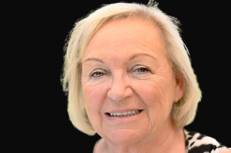 Attractive friendly elderly blond woman. Looking at the camera with a smile, close up head shot against black background royalty free stock image