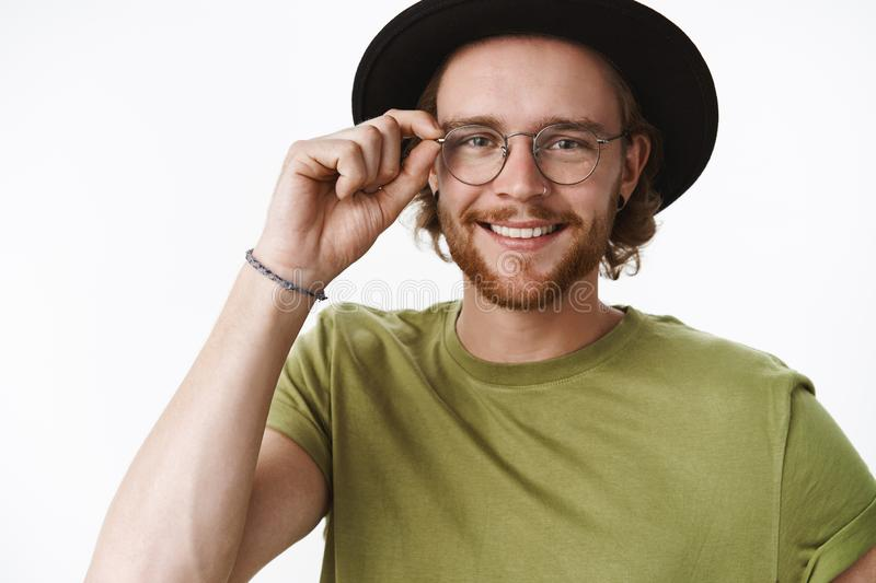 Attractive friendly-looking charismatic young bearded guy in glasses and hat touching frames of eyewear and smiling stock photos