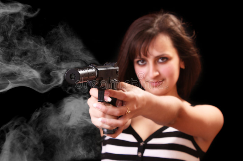 Attractive girl aiming with gun with smoke stock photos