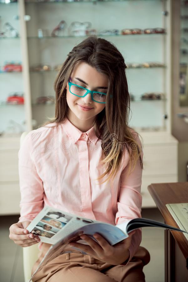 Attractive girl on appointment in eye specialist office. Portrait of european young brunette customer sitting in glasses stock images