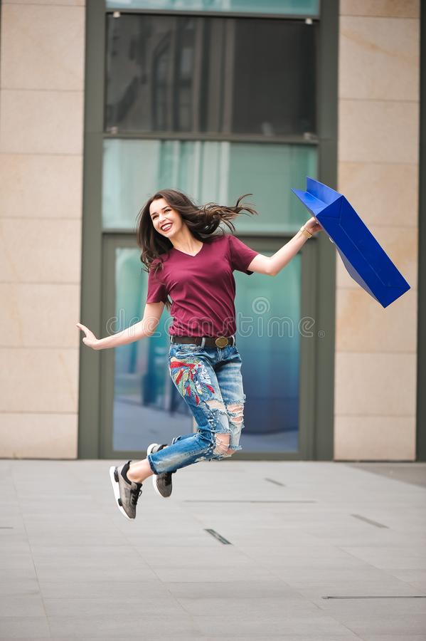 Attractive girl with Bags in her hand. Woman and shopping. Beautiful model goes through the city on foot. stock images