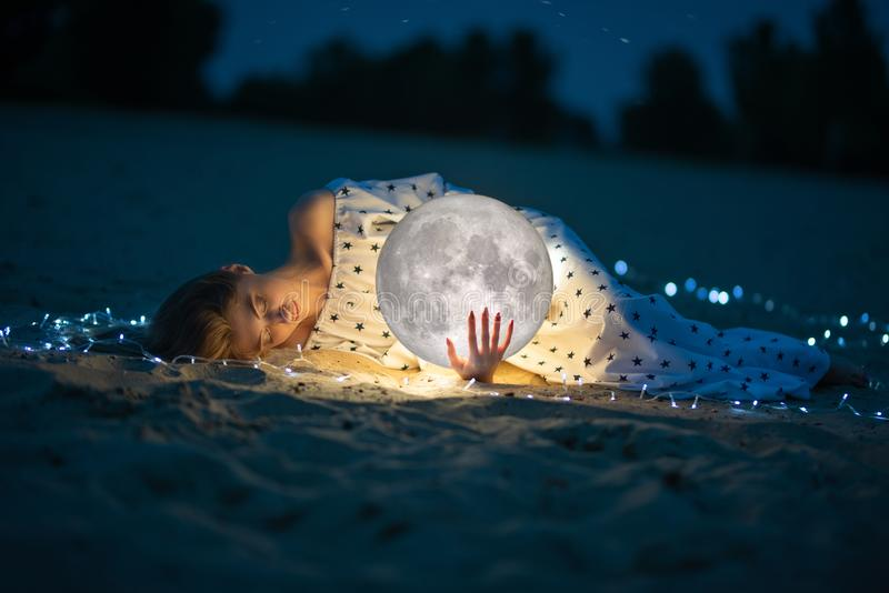 Attractive girl on the beach and hugs the moon, with a starry sky. Artistic photo royalty free stock image