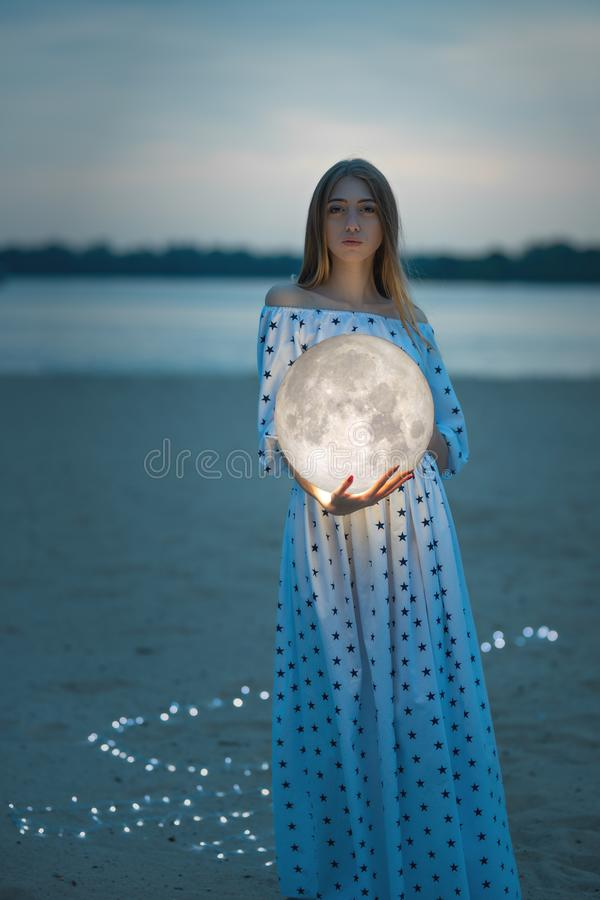 Attractive girl on the beach and hugs the moon, with a starry sky. Artistic photo stock photos