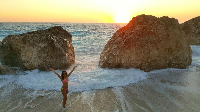 Attractive girl on the beach. Young attractive brunette between rocks on a rocky beach on the Greek island of Lefkada, Ionian sea stock images