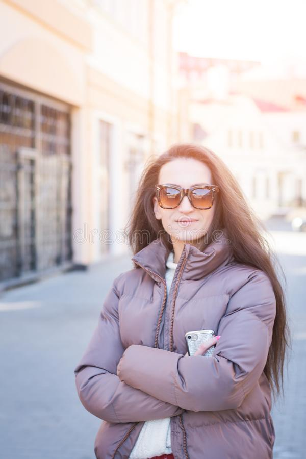Attractive girl with black hair and sunglasses looks into the camera. Attractive portrait girl with black hair and sunglasses looks into the camera on a city stock photos