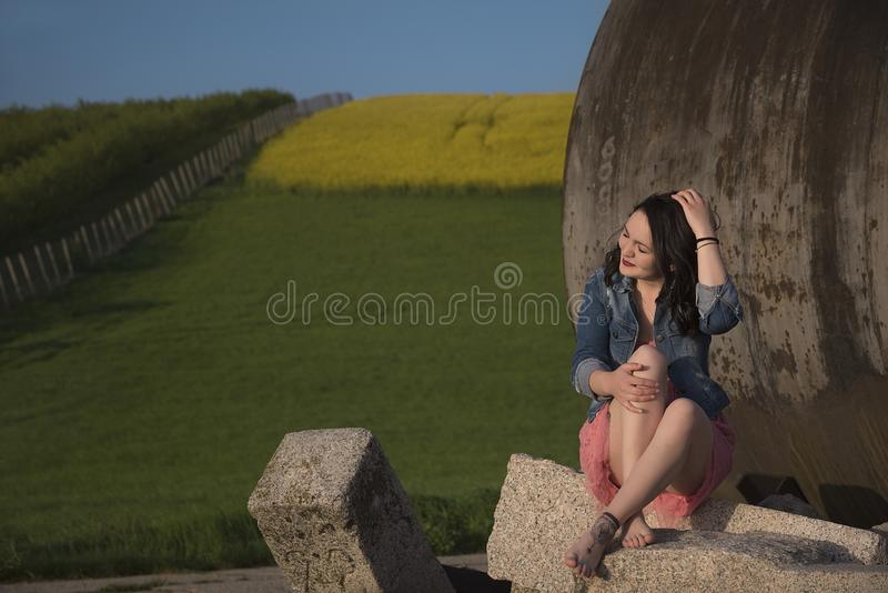 Beautiful smiling woman on a rock at sunset royalty free stock photography