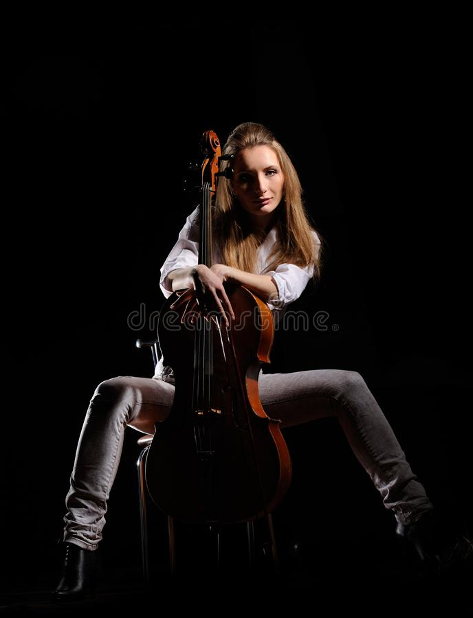 Attractive girl with cello isolated over black background. Adult, art, face, fashion, fiddle, gaze, glamorous, instrumental, lady, leisure, luxury, model royalty free stock image