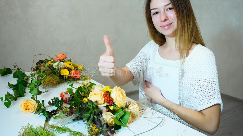 Cute young woman holding florist with smile and posing with gest royalty free stock photography