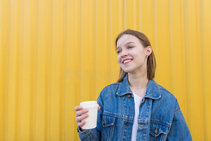 An attractive girl with a cup of coffee in her hands stands on the background of a yellow wall and smiles stock photography