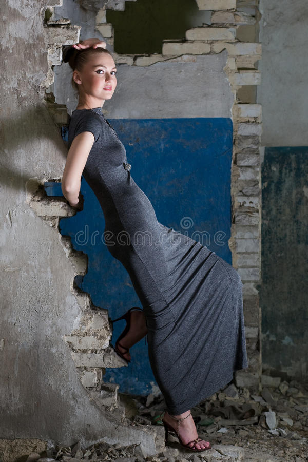 Attractive girl in dress posing in the slums stock photo