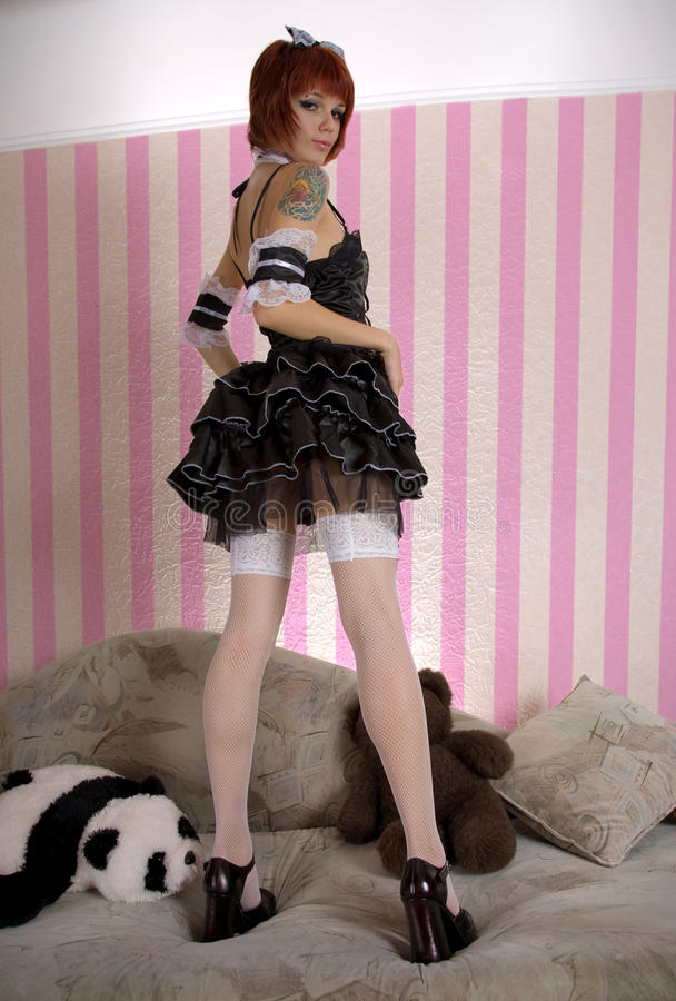 Attractive girl dressed like Gothic Lolita. In funny interior stock images
