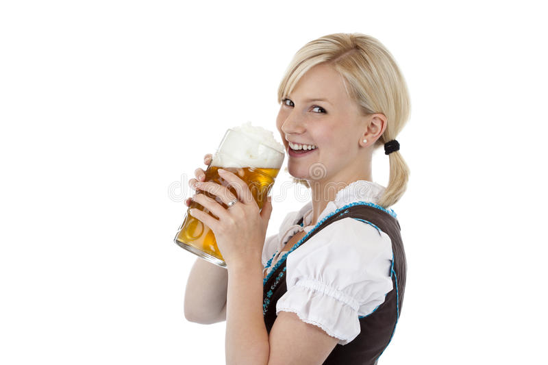 Attractive girl drinking out of beer stein. Attractive blond girl drinking out of oktoberfest beer stein. Isolated on white background royalty free stock image