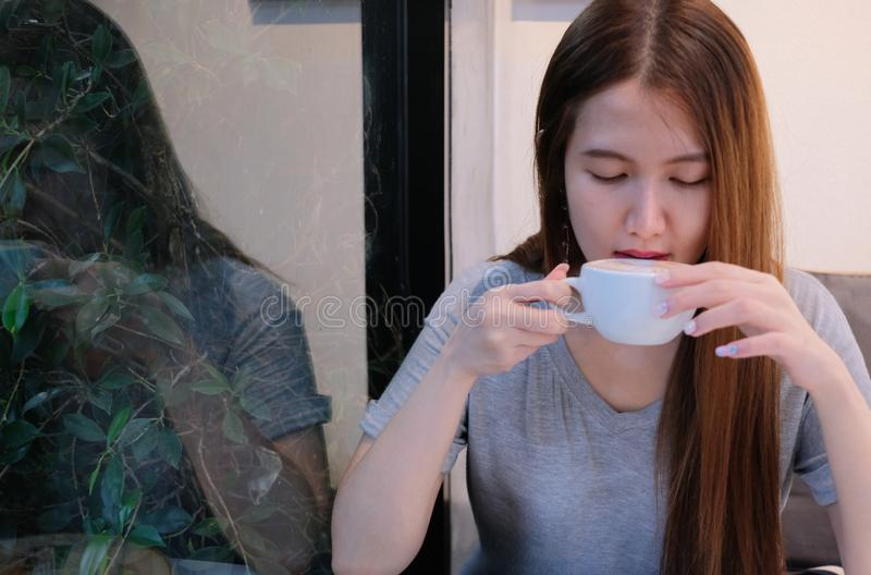 Attractive girl drinks coffee in garden house royalty free stock images