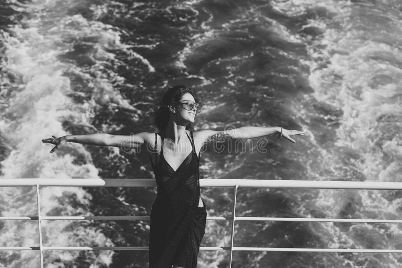 Attractive girl feels free and enjoy summer vacation. Freedom concept. lady stands on deck of cruise liner with sea stock image