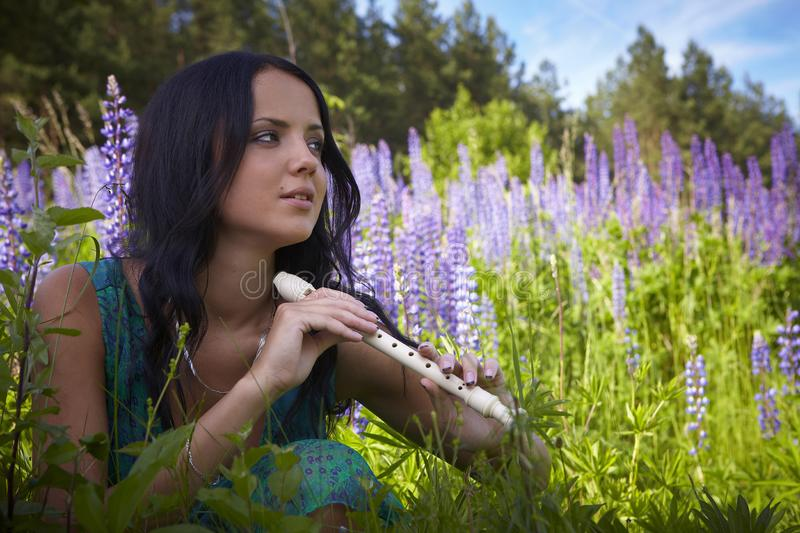 Attractive girl with flute sitting in summer field