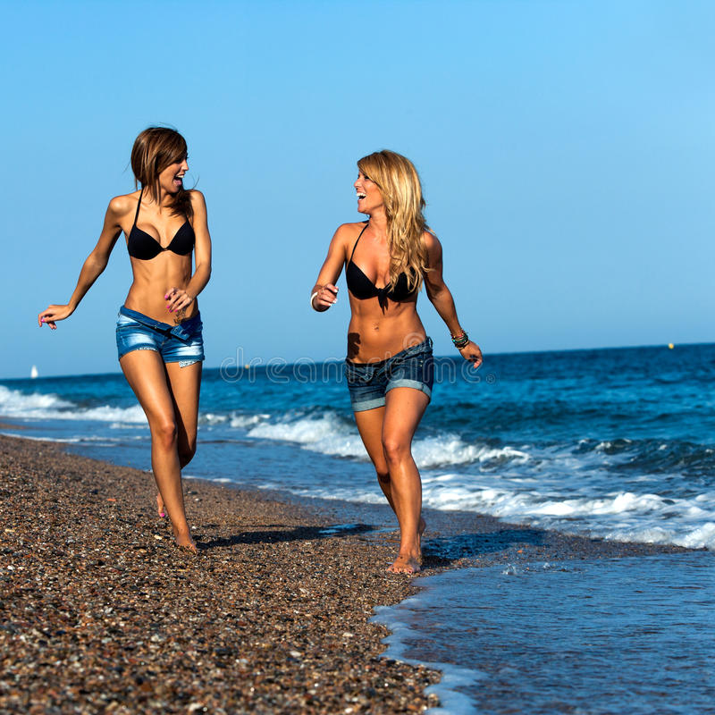 Attractive girl friends running along seaside. royalty free stock photos