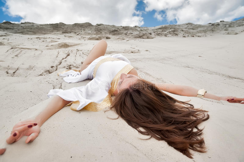 Attractive girl in greek tunic. Young pretty woman in greek tunic lies on sand blindly royalty free stock images