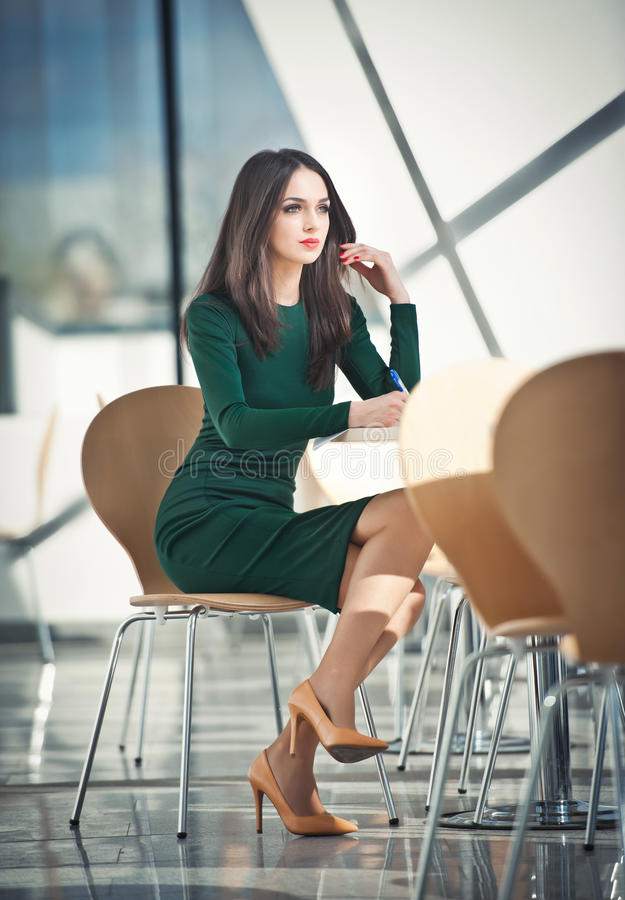 Attractive girl in green dress sitting on chair writing stock photos