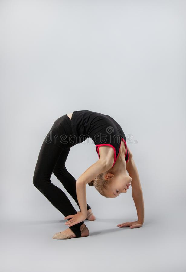 Attractive girl gymnast performs a complex exercise. Flexibility, stretching stock photography