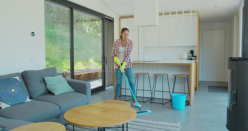 Attractive girl is listening to music and dancing wih mop during domestic work, she is mopping floor at home and having royalty free stock photography