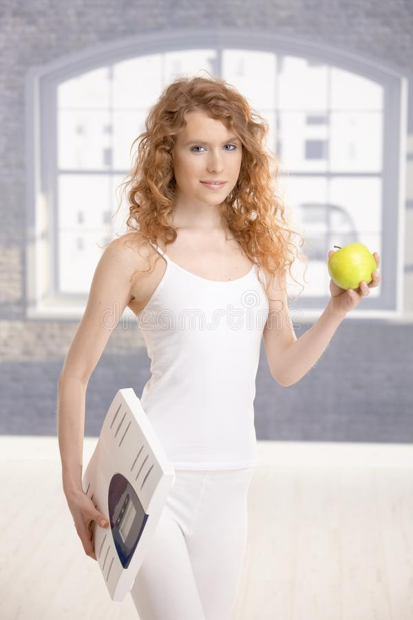 Attractive girl holding apple and scale in hands. Living healthy royalty free stock images