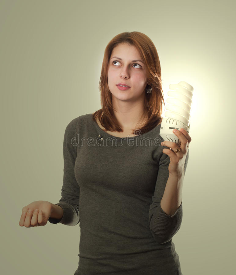 Attractive girl holding a fluorescent tube. On a white background royalty free stock images