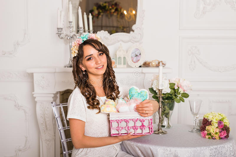 Attractive girl holding heart-shaped pillow. Attractive young pretty woman holding heart-shaped pillow royalty free stock images