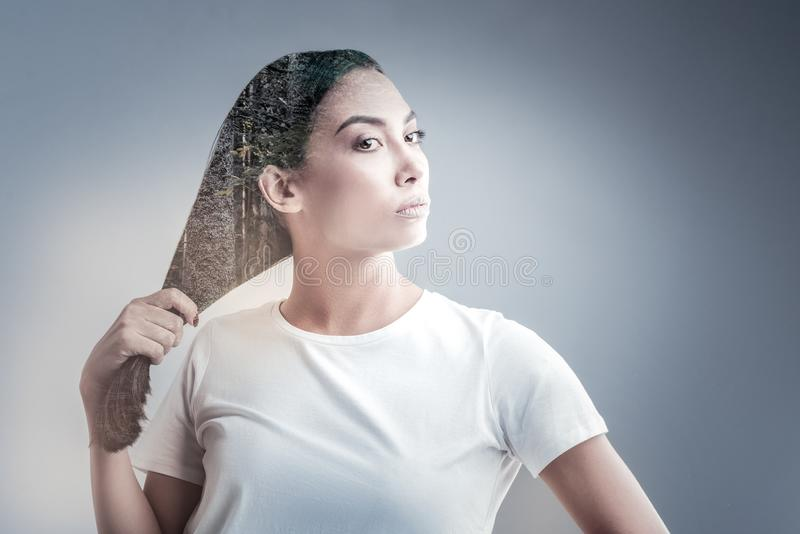 Attractive girl holding her long hair. Strong hair. Serious female person pressing lips and turning head while standing against suburban surrounding royalty free stock image