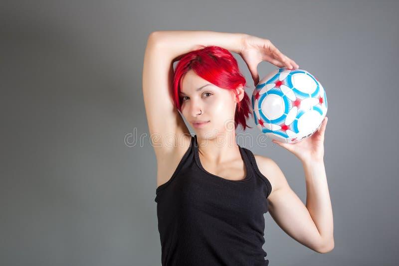 Attractive girl holding a soccer ball stock photos