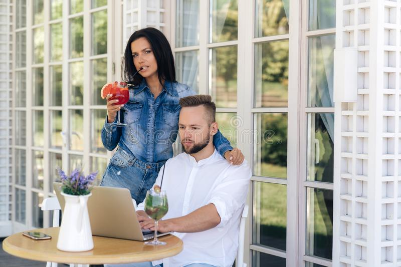 An attractive girl hugs her boyfriend in the cafe, drinks a delicious cocktail. A freelance man is busy working on a stock photo