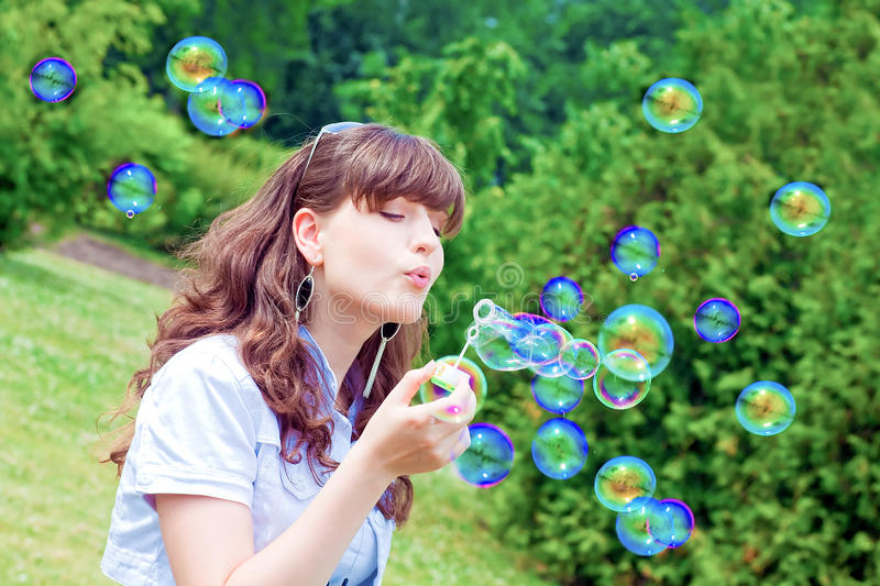 Download Attractive Girl Inflating Colorful Soap Bubbles Stock Image - Image: 20047675
