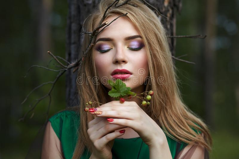 Attractive girl with a little bush of strawberries in her hands royalty free stock images