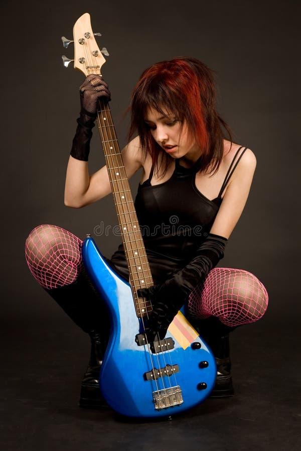 Attractive girl looking at bass guitar stock photos