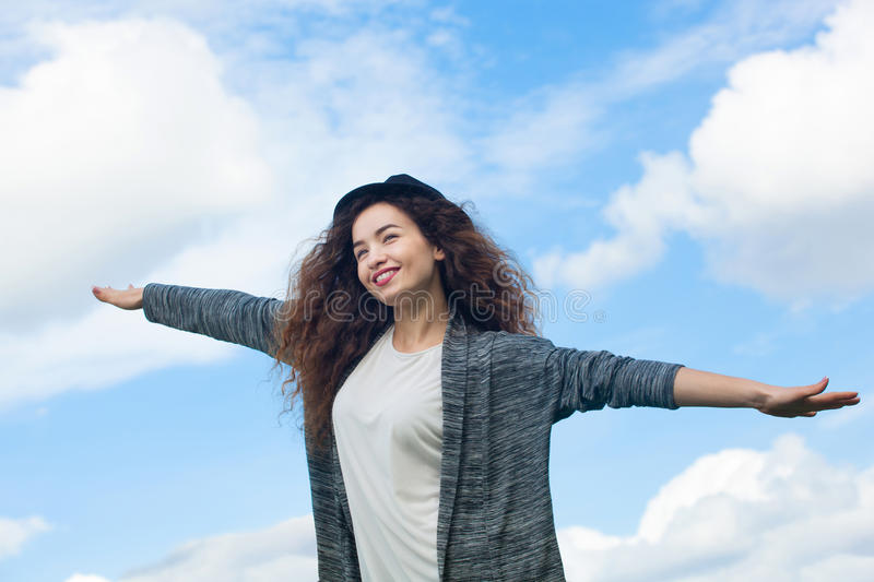 Attractive girl with outstretched hands in the hand in a black hat, smiling on the background of sky. stock photo