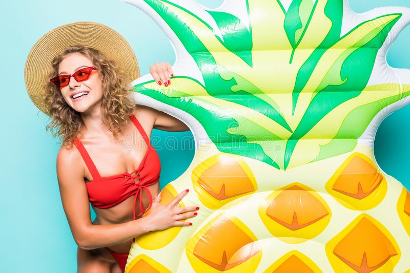 Attractive girl with a perfect body in a red bikini, hat, sunglasses on a blue background. stock photos