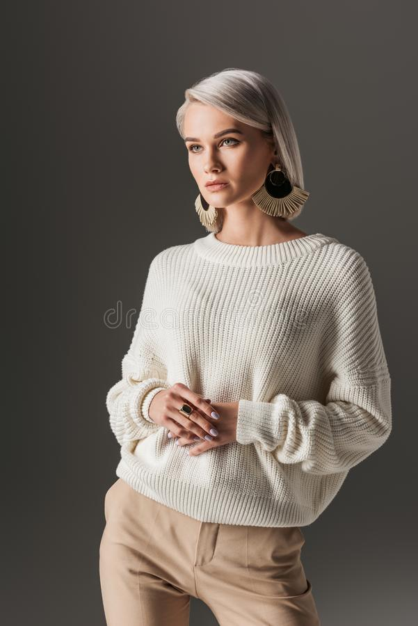 Attractive girl posing in white autumn sweater and round earrings. Isolated on grey stock photography